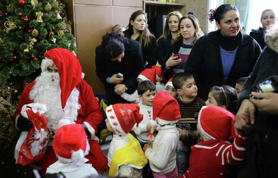Syrian children and their partents gather around Santa Claus at a kindergarten in Damascus, on December 19, 2013. Photo: LOUAI BESHARA, AFP/Getty Images / AFP