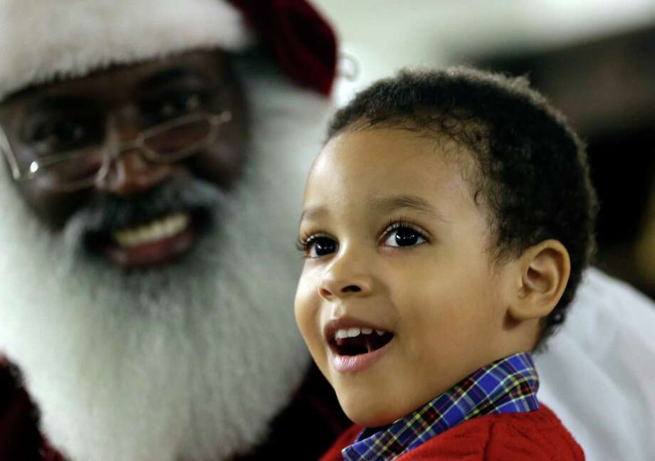 In this Tuesday, Dec. 17, 2013 photo, Dee Sinclair, who bills himself as the real black Santa, delights 4-year-old Joe Morris IV, in Atlanta. Fusing the icon of the long-white beard and red suit from American artist Norman Rockwell and later Coca-Cola, in recent years the new Santas incorporate their own ethnic take on the Christmastime figure with various interpretations. Photo: John Bazemore, Associated Press / AP