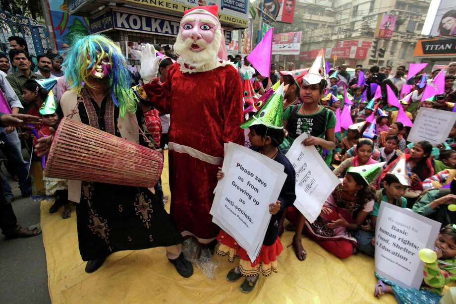 A folk singer performs and a man dressed as Santa Claus waves as underprivileged children wear festive hats and hold placards during a sit-in demonstration demanding basic human rights in Kolkata, India, Thursday, Dec. 19, 2013. The demonstration held ahead of Christmas was organized by Bangiya Christian Pariseba or Bengal Christian Confederation. Photo: Bikas Das, Associated Press / AP