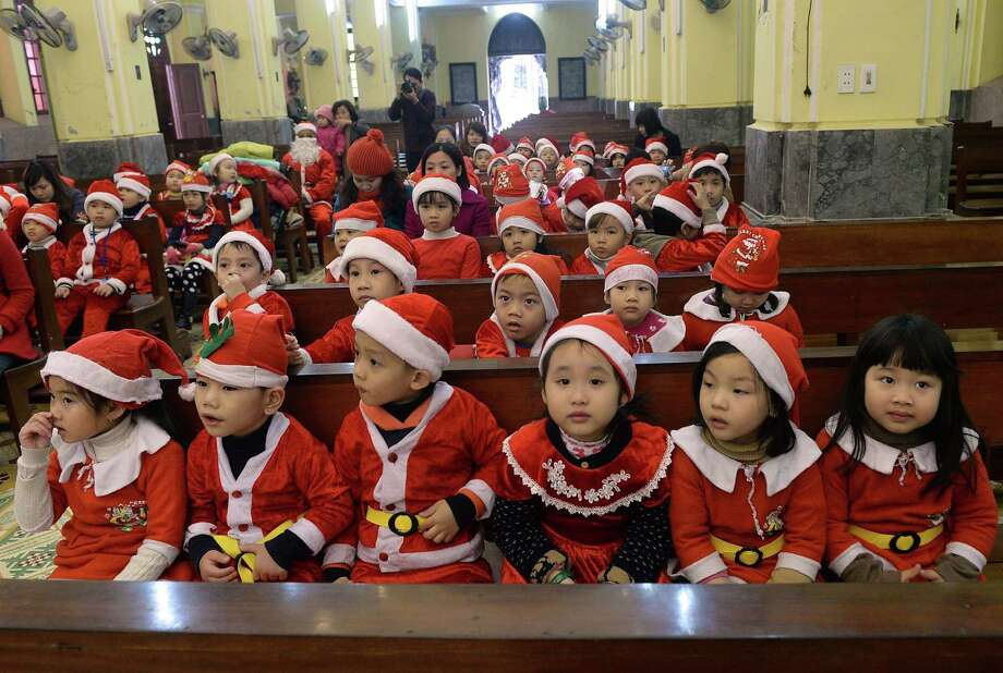 Children wearing Santa Claus costumes from a kindergarten listen to a priest (not pictured) explaining the history of the Christmas holiday at a Catholic church in Hanoi on December 19, 2013. Photo: HOANG DINH NAM, AFP/Getty Images / AFP
