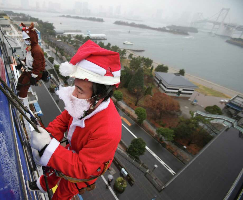 Window cleaners dressed as Santa Claus and reindeer descend the glass exterior of a shopping mall in Odaiba, the Tokyo Bay area, Thursday, Dec. 19, 2013, as part of the annual seasonal event. Photo: Koji Sasahara, Associated Press / AP