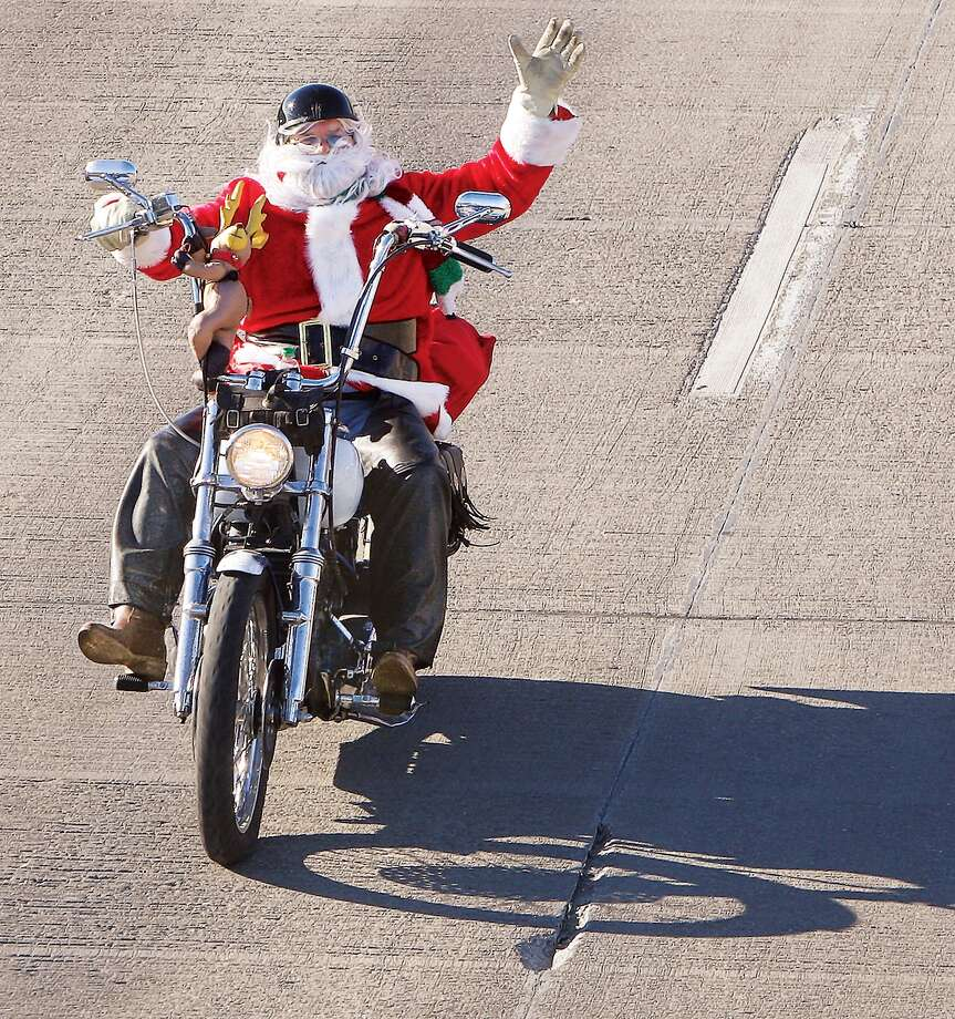 Herman Morgan of Florissant, Mo., takes advantage of the moderation in the weather, Wednesday, Dec. 18, 2013, to dress up as Santa Claus and go for a ride through Alton, Ill., on his motorcycle. Morgan makes his way up Landmarks Blvd. waving to traffic after taking a leisurely ride down East Broadway in his bright red suit. Photo: John Badman, Associated Press / The Telegraph