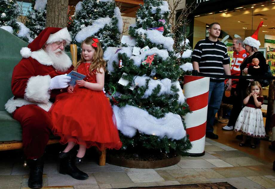 Santa gives a book to Lucy Emitario, age 6, during a visit to Santa's Wonderland House inside Flatirons Crossing Mall, in Broomfield, Colo., Wednesday, Dec. 18, 2013. Photo: Brennan Linsley, Associated Press / AP