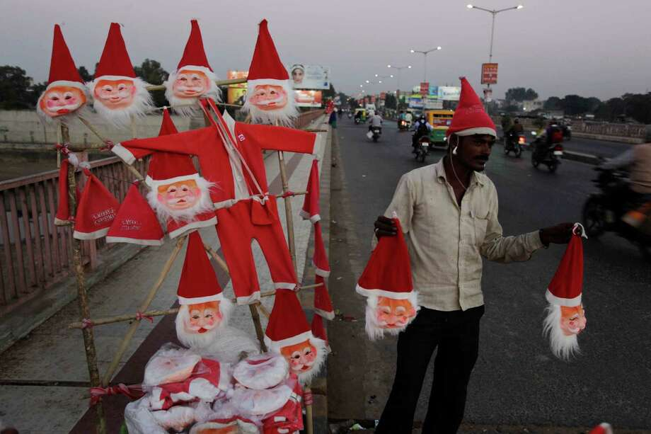 An man sells Santa Claus masks on a road side ahead of Christmas in Ahmadabad, India, Wednesday, Dec. 18, 2013. Christmas is a national holiday in India and celebrated with much fanfare. Photo: Ajit Solanki, Associated Press / AP