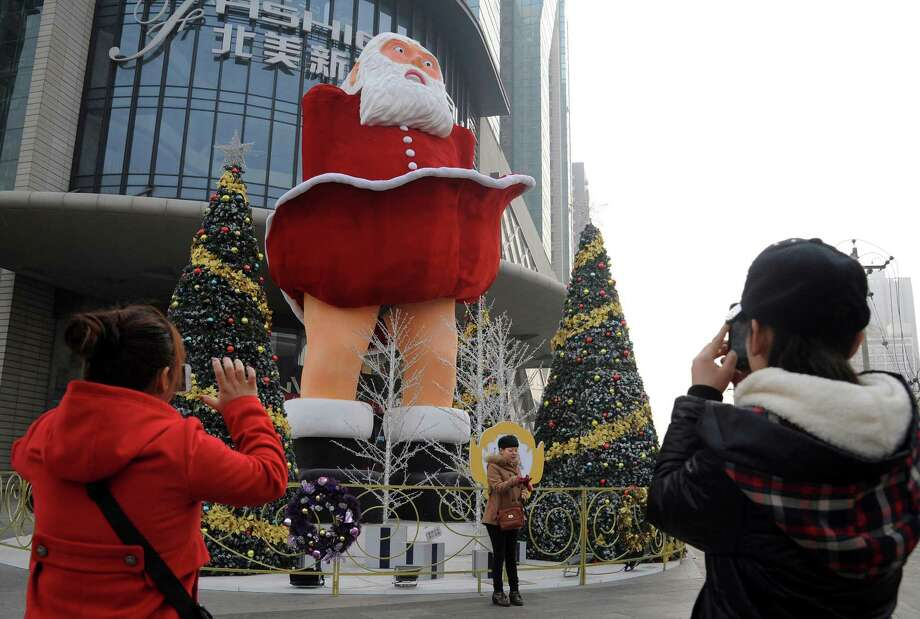 Residents take photos of a Santa Claus statue imitating Marilyn Monroe's famous pose outside a department store in Taiyuan in north China's Shanxi province Tuesday Dec. 17, 2013. Photo: Associated Press / CHINATOPIX