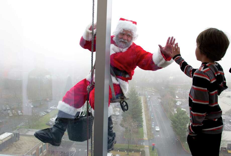 Phillip Hartlip, 9, a patient at Randall Children's Hospital from Camas, Wash., shares a moment with Santa in Portland, Ore. Santa and his elves made the windows of the Randall Children's Hospital at Legacy Emanuel extra bright Monday, Dec. 16, 2013. The window washers, employed by Millennium Building Services, have been washing the hospital's windows for 22 years. Santa, Jason Kirk, was accompanied by some of his elves Dustin Atkins and Andrew Nava. Photo: Beth Nakamura, Associated Press / The Oregonian