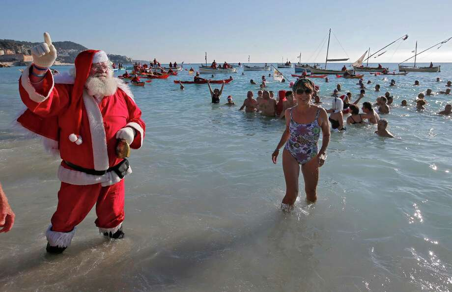 2A man dressed as Santa Claus poses for photographers as people bathe during the traditional Christmas bathe on the Mediterranean sea at at Nice, southeastern France, Sunday, Dec. 15, 2013. Temperature of the water was 60 degrees Fahrenheit. Photo: Lionel Cironneau, Associated Press / AP