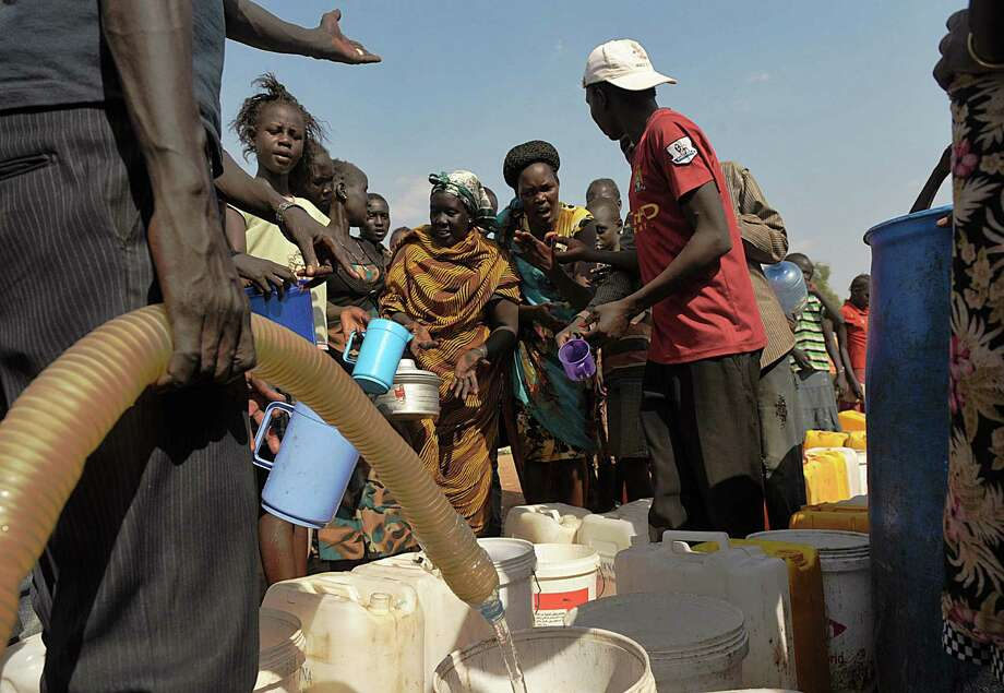South Sudanese women jostle to get water being distributed at the United Nations Mission in South Sudan compound. Tension remains high, fueling an exodus of both local and foreign residents from the South Sudanese capital. Photo: Tony Karumba / Getty Images / TONY KARUMBA