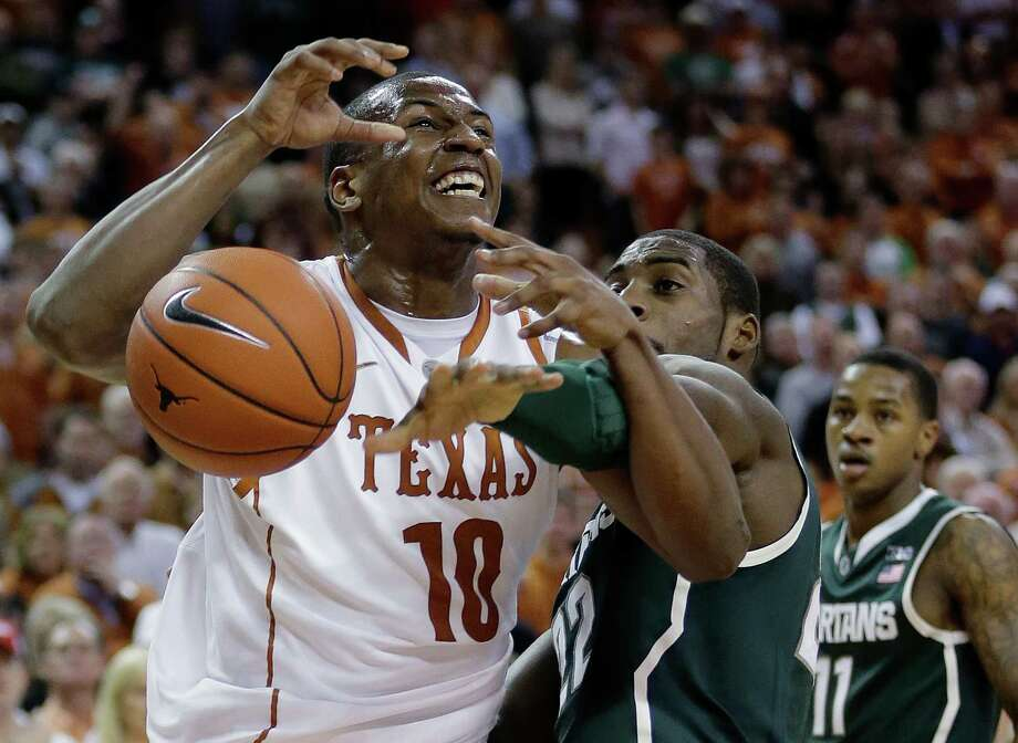 Texas' Jonathan Holmes (10) is fouled by Michigan State's Branden Dawson as he goes up for a shot in the first half of Saturday's game in Austin. Photo: Eric Gay, STF / AP