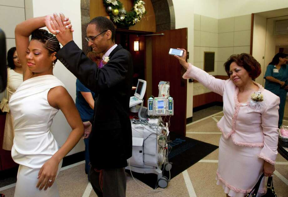 Timothy Lewis dances with daughter Lolaycia after she and Melmiah Walker wed Saturday in the chapel at Houston Methodist Hospital. Awaiting a heart transplant, Lewis had promised to walk her down the aisle. Photo: Brett Coomer, Staff / © 2013 Houston Chronicle