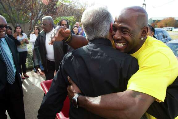 Former Green Bay Packers wide receiver Donald Driver, right, embraces Star of Hope's Scott Arthur after delivering food to the residents there Thursday.