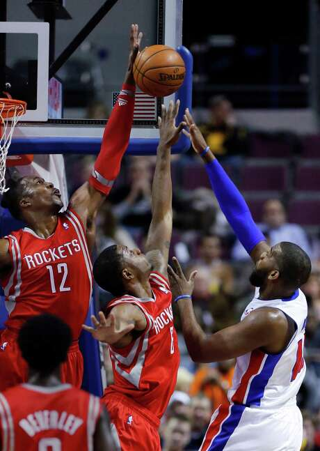 Rockets center Dwight Howard (12) goes over the back of teammate Terrence Jones to block a shot by Pistons center Greg Monroe, one of his three in the game. Photo: Duane Burleson, FRE / FR38952 AP