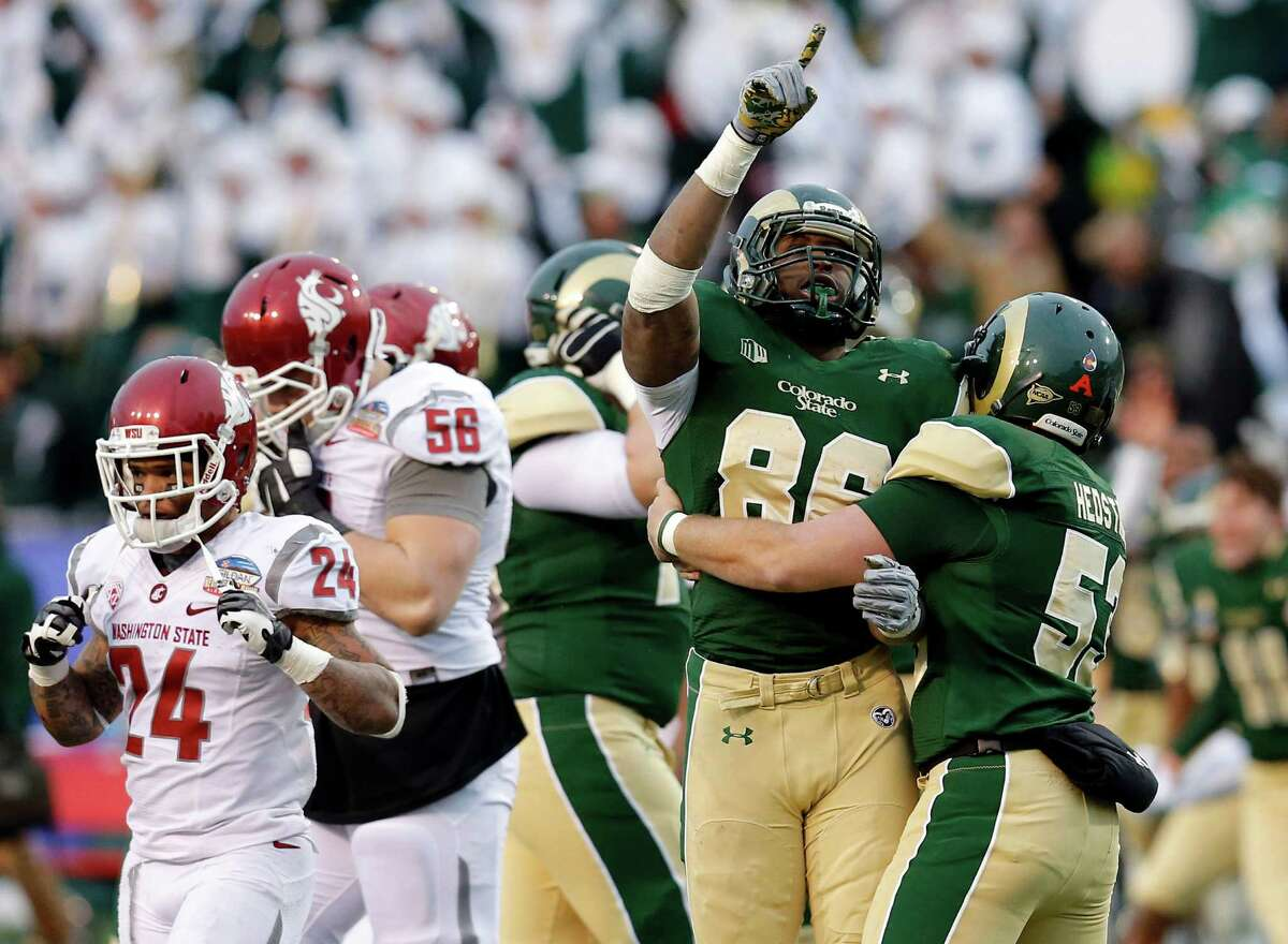 Colorado State's Kivon Cartwright (86) and Tanner Hedstrom (53) celebrate their win as Washington State Cougars running back Theron West (24) and Joe Dahl (56) leave the field after the NCAA New Mexico Bowl college football game, Saturday, Dec. 21, 2013, in Albuquerque, N.M. Colorado State won 48-45.(AP Photo/Matt York) ORG XMIT: NMMY125