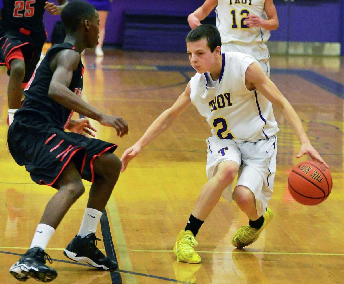 Troy's #2Ryan Carmello, at right, drives around past Proctor J'Von Evans during Saturday's game at Troy High Dec. 21, 2013, in Troy, NY. (John Carl D'Annibale / Times Union)
