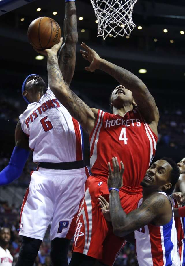 Rockets center Greg Smith (4) goes to the basket against Pistons forward Josh Smith (6) and guard Brandon Jennings. Photo: Duane Burleson, Associated Press