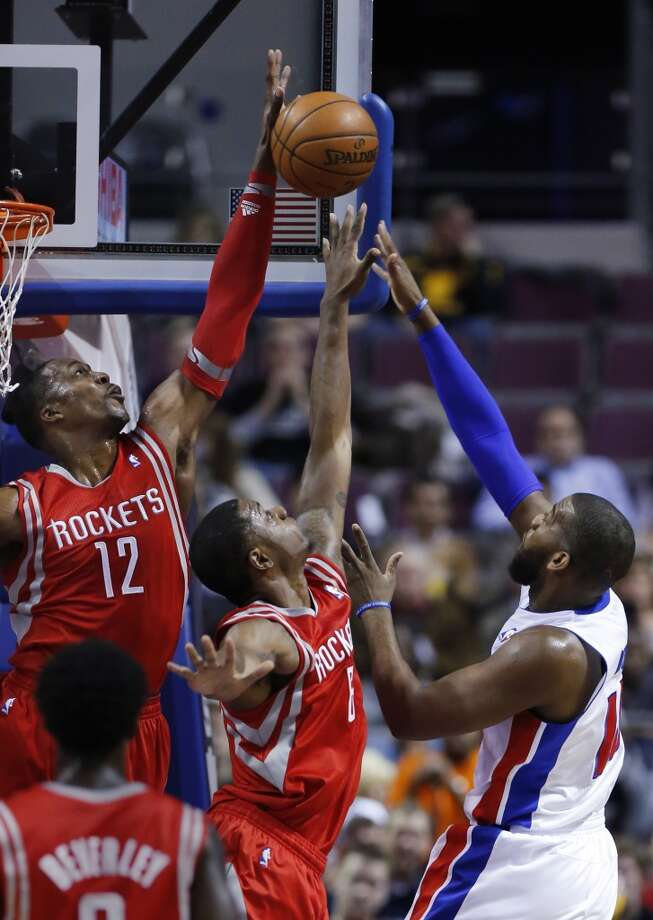Rockets center Dwight Howard (12) blocks a shot by Pistons center Greg Monroe, right, as Rockets forward Terrence Jones (6) helps defend. Photo: Duane Burleson, Associated Press