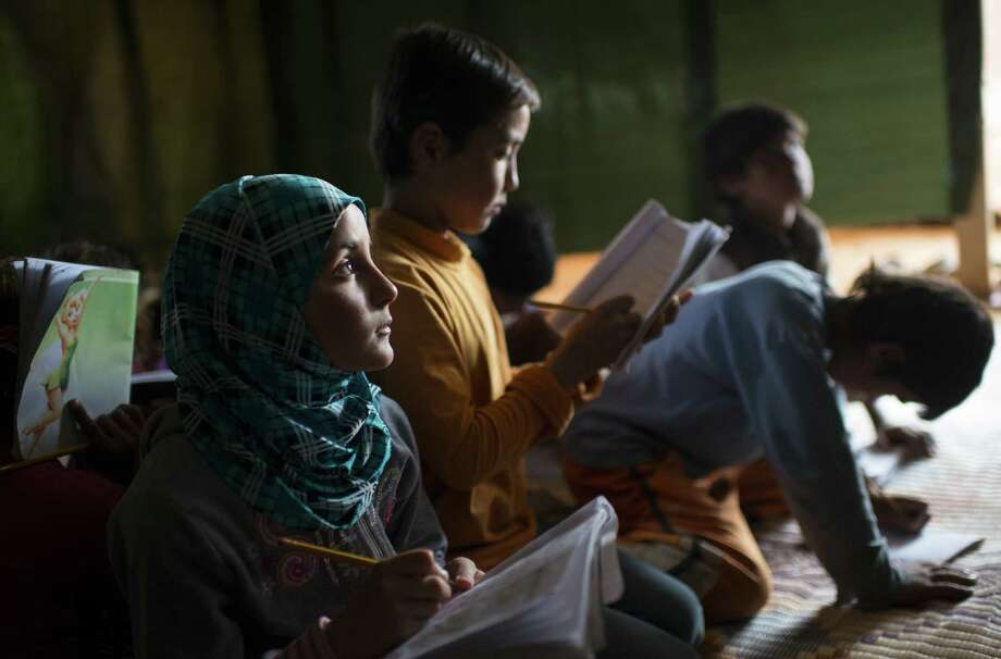 Children work on their lessons at a tent school for Syrian refugees run by a local charity in Baalbek, Lebanon. These children are fortunate. Of the 865,000 Syrian refugee children across the region, about 7 in 10 are not enrolled in a school, Unicef estimates. Photo: Lynsey Addario / New York Times / NYTNS