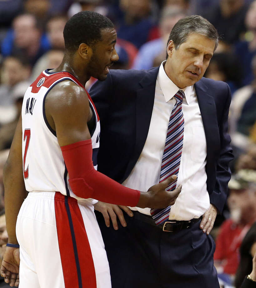 Wizards coach Randy Wittman, talking with star guard John Wall, probably needs to make the playoffs in the weak Eastern Conference to retain his job. Photo: Alex Brandon / Associated Press / AP
