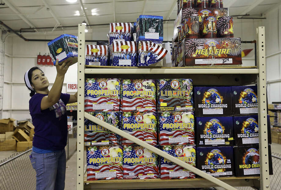 Angie Alvarado stocks shelves at the Mr. W Fireworks warehouse at Interstate 37 South and Loop 1604. Nonprofits raise funds by operating fireworks stands. Photo: Edward A. Ornelas / San Antonio Express-News / © 2013 San Antonio Express-News