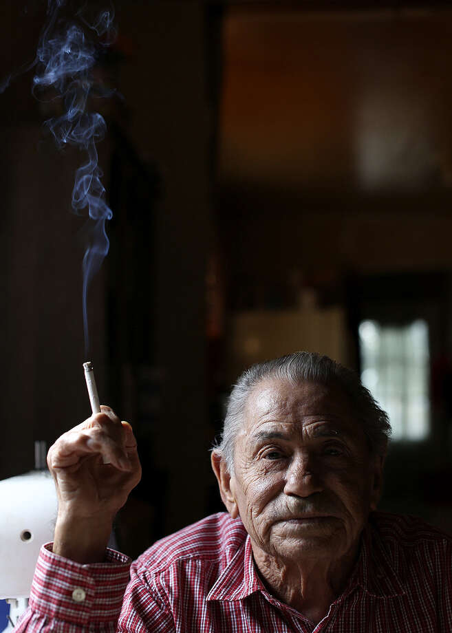 Smoke in hand, retired jockey Heriberto Hinojosa relaxes at his home in Brownsville. During his racing career, he played cards at the Waldorf and drank with Hollywood stars. Photo: Lisa Krantz, San Antonio Express-News / San Antonio Express-News