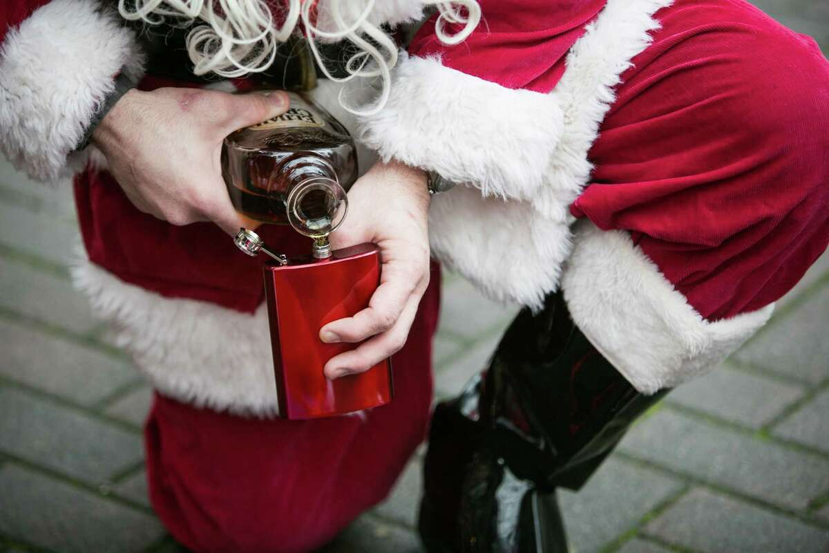 Santa Claus pours a drink to help warm the pack of jolly elves.