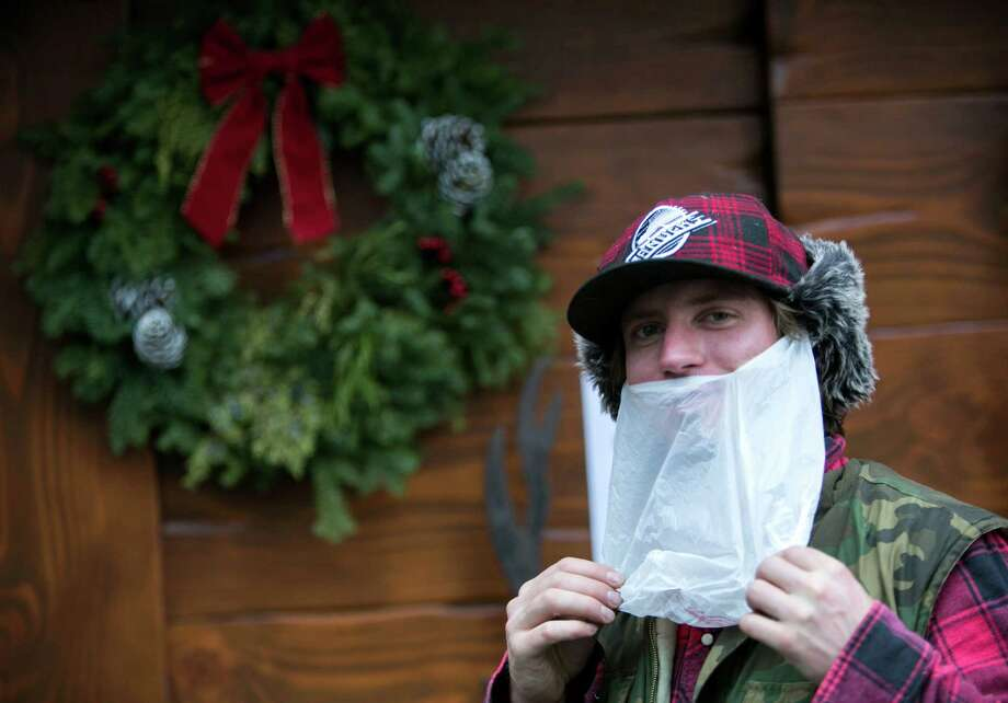 Garrett Mugford wears a plastic bag as his makeshift Santa beard. Cover charges were waived at bars and clubs for people dressed as the jolly elf.  Photo: JOSHUA TRUJILLO, SEATTLEPI.COM / SEATTLEPI.COM
