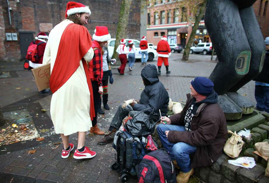 A participant dressed as Jesus passes men sitting in Occidental Square. He handed them each a candy cane. Photo: JOSHUA TRUJILLO, SEATTLEPI.COM / SEATTLEPI.COM