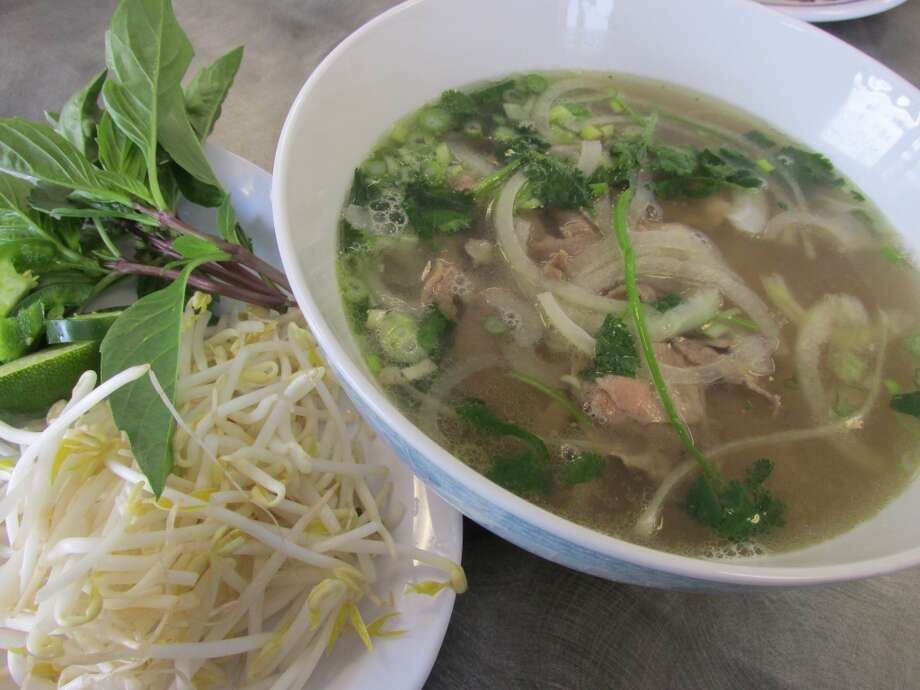Pho Tai Nam Gan (#15): Noodle soup with round eye steak, well done brisket and soft tendon, served with basil, lime, jalapenos and bean sprouts at Pho Ha in Nederland. Photo: Cat5