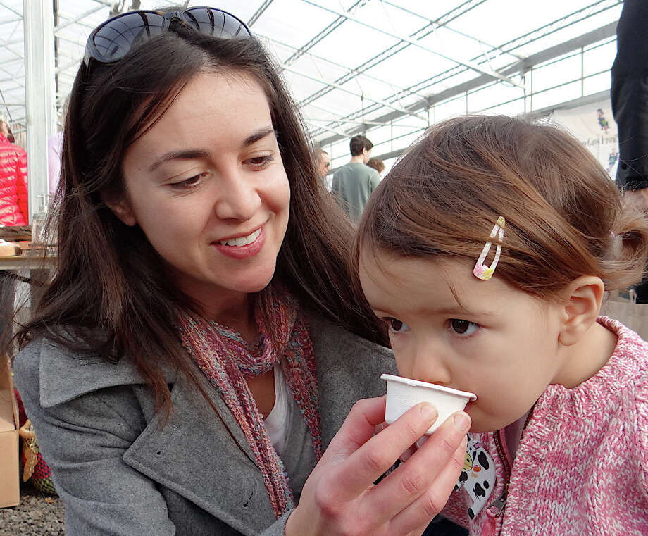 Melissa Whitehead and daughter Sophia, 2, sample turmeric ginger tea at the Westport Winter Farmers Market. Photo: Mike Lauterborn / Westport News contributed