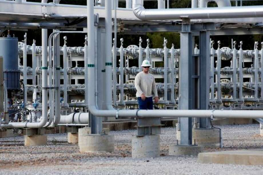 A worker walks past a CO2 manifold at Denbury Resources Inc.'s, Tinsley Facility in Tinsley, Miss. Photo: Rogelio V. Solis / Associated Press