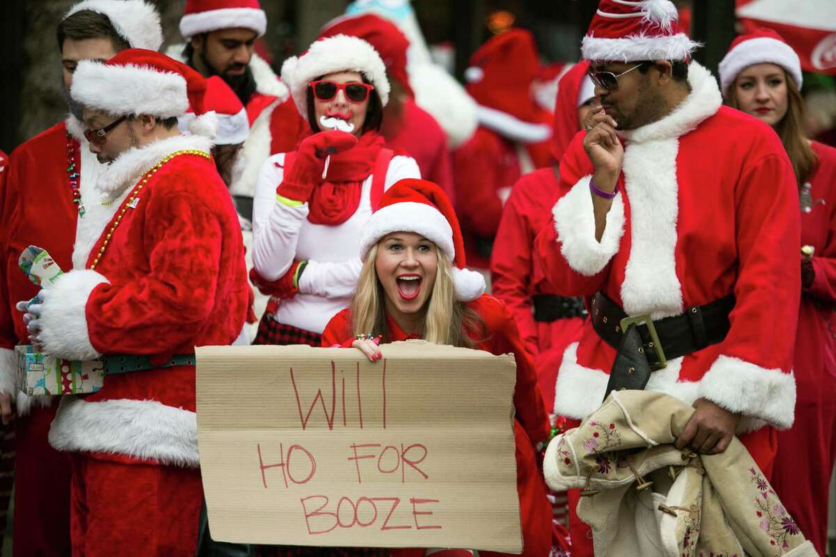 A participant holds up one of the naughty signs passed around during Santarchy 2013, also known as SantaCon, a bar crawl for participants dressed as jolly elves. Hundreds of Santa Claus impersonators earned a spot on the naughty list during the annual pub crawl in downtown Seattle. Photographed on Saturday, December 21, 2013 in downtown Seattle.