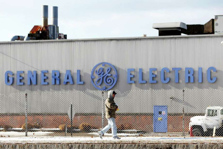 In this Dec. 11, 2013 photo, a man walks past the General Electric plant in Fort Edward, N.Y. GE has been a big presence in this little upper-Hudson River town for almost 70 years, employing generations and leaving a $2 billion mess in the river. Now GE is moving its operations to Florida. Photo: Mike Groll, AP / AP