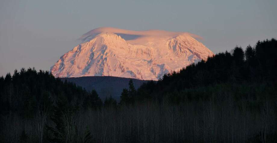 This Jan. 8, 2012 file photo shows Mount Rainier taking on a rosy glow near sunset as viewed from Eatonville, Wash. Mount Rainier National Park managers will try to maintain daily access to the park's most popular winter destination. There is a sledding area, snowshoeing, snow camping, skiing and snowboarding and a visitor center at Paradise. People visiting Paradise should leave no later than 4:30 p.m. PST to give themselves enough time to safely drive down to Longmire, and sooner if road conditions are not optimal. Photo: Ted S. Warren, AP / AP