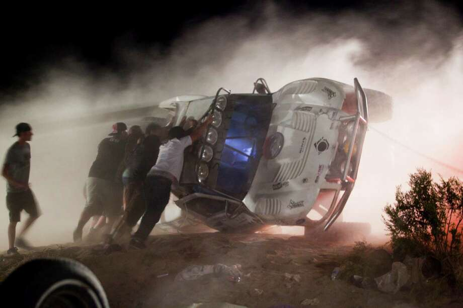 In this Aug. 15, 2010 file photo, people push an overturned off-road race truck upright after it went out of control and ran into a crowd of spectators during a race in Lucerne Valley, Calif. A lawyer said Wednesday, Dec. 18, 2013, that a global settlement has been reached to pay $5.8 million to the families of eight people killed and 12 injured in the California desert off-road race crash. Attorney Katherine Harvey-Lee said an agreement was reached in mediation with federal government lawyers. Harvey-Lee says the agreement still must be approved by the Department of Justice and signed off by a judge. She says she represents three injured spectators and the father of one of those killed. Photo: Francis Specker, AP / FR123675 AP