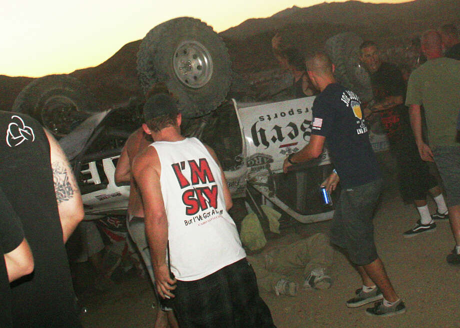 In this Aug. 14, 2013 file photo, bystanders rush to help a victim, center, pinned under an overturned off-road race truck moments after it plowed into a crowd after sailing off a jump at the California 200 off-road race in Lucerne Valley Calif.  A lawyer said Wednesday, Dec. 18, 2013, that a global settlement has been reached to pay $5.8 million to the families of eight people killed and 12 injured in the California desert off-road race crash. Attorney Katherine Harvey-Lee said an agreement was reached in mediation with federal government lawyers. Harvey-Lee says the agreement still must be approved by the Department of Justice and signed off by a judge. She says she represents three injured spectators and the father of one of those killed. Photo: Dave Conklin, AP / AP