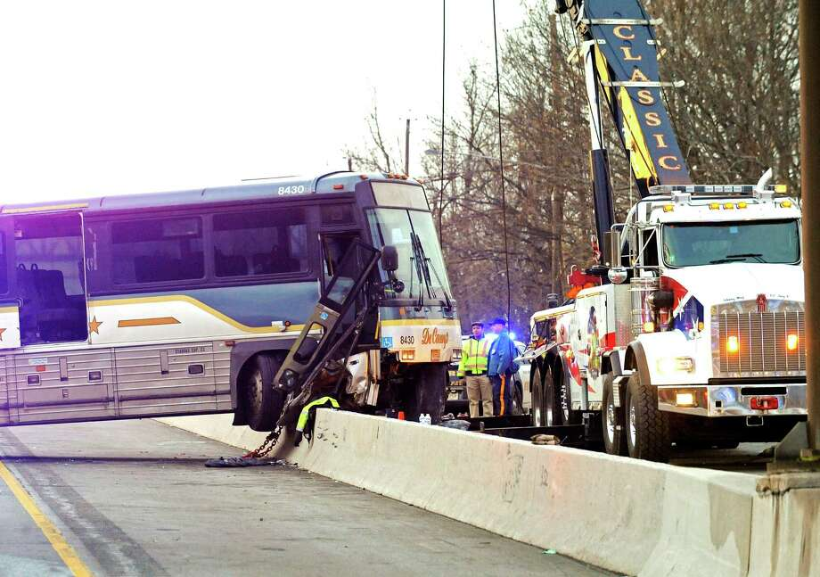 Workers attempt to free a bus that crashed onto the divider on Route 3 eastbound Thursday, Dec. 19, 2013, in Clifton, N.J. Photo: Bill Kostroun, AP / FR51951 AP