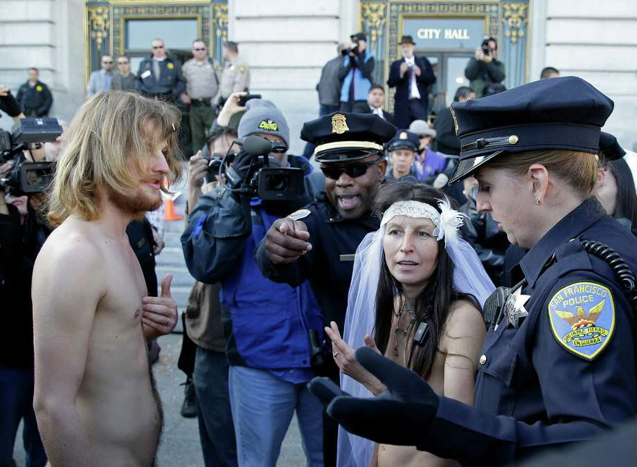 San Francisco police lead away Gypsy Taub, right, and Jaymz Smith, left, to a van after their nude wedding outside City Hall, Thursday, Dec. 19, 2013, in San Francisco. Taub, the face and body of San Francisco's nude rights movement, tied the knot outside City Hall and was later cited and released by police. Taub, a mother of three who conducts nude interviews on public access TV, has been arrested repeatedly for violating the city's public nudity ban. Photo: Eric Risberg, AP / AP2013
