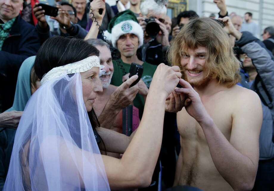 Gypsy Taub, left, places a ring on the finger of Jaymz Smith, right, during their nude wedding outside City Hall, Thursday, Dec. 19, 2013, in San Francisco. Taub, the face of San Francisco's nude rights movement, tied the knot outside City Hall and was later cited and released by police. Taub, a mother of three who conducts nude interviews on public access TV, has been arrested repeatedly for violating the city's public nudity ban. Photo: Eric Risberg, AP / AP2013