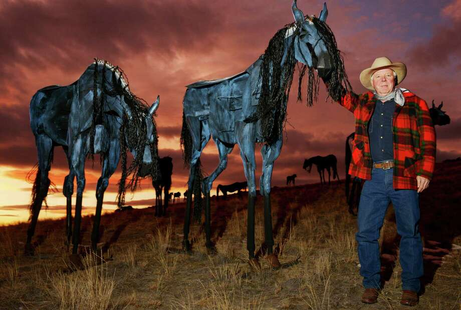 In this photo taken on Monday, Dec. 16, 2103, sculptor Jim Dolan, from Belgrade, Mont., poses for a photo with his steel horse herd sculptures that are on display on a hillside near Three Forks, Mont. Dolan, who spent about 15 months making them, recently discovered that three of his sculptures have been stolen. Photo: Mike Greener, AP / Bozeman Daily Chronicle
