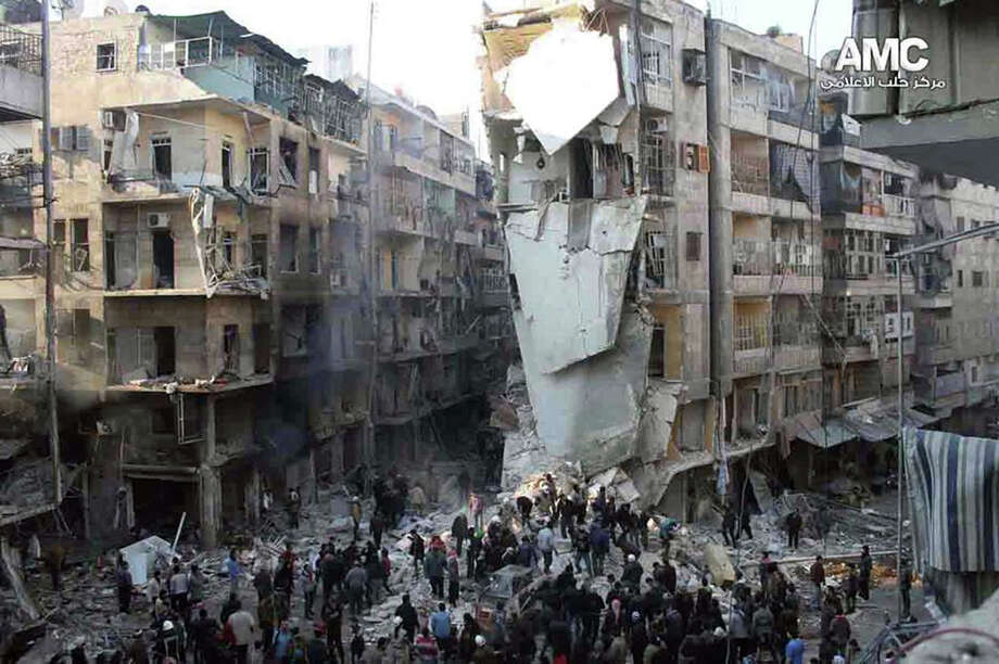 In this Tuesday, Dec. 17, 2013 citizen journalism image provided by Aleppo Media Center, AMC, and released Wednesday, Dec. 18, 2013, which has been authenticated based on its contents and other AP reporting, Syrians inspect the rubble of damaged buildings following a Syrian government airstrike in Aleppo, Syria. Syrian warplanes dumped explosive-laden barrel bombs over opposition-held parts of the northern city of Aleppo on Wednesday, the fourth day of a relentless offensive to drive rebels out of the contested city, activists said. The country's conflict, now in its third year, appears to have escalated in recent weeks as both sides maneuver ahead of next month's planned peace talks and ignore calls for a cease-fire. Photo: HOEP, AP / AP2013