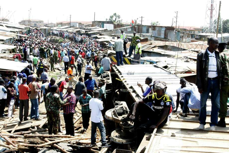 Kenyans gather around the remains of a house which lies on the train tracks next to a train carriage on its side after a cargo train derailed in Nairobi, Kenya, Sunday, Dec. 22, 2013. Several people have been injured after a cargo train crashed into homes in the sprawling Nairobi slum of Kibera. The train is reported to have derailed while passing through the slum, one of Africa's largest, on Sunday morning. Photo: Khalil Senosi, AP / AP