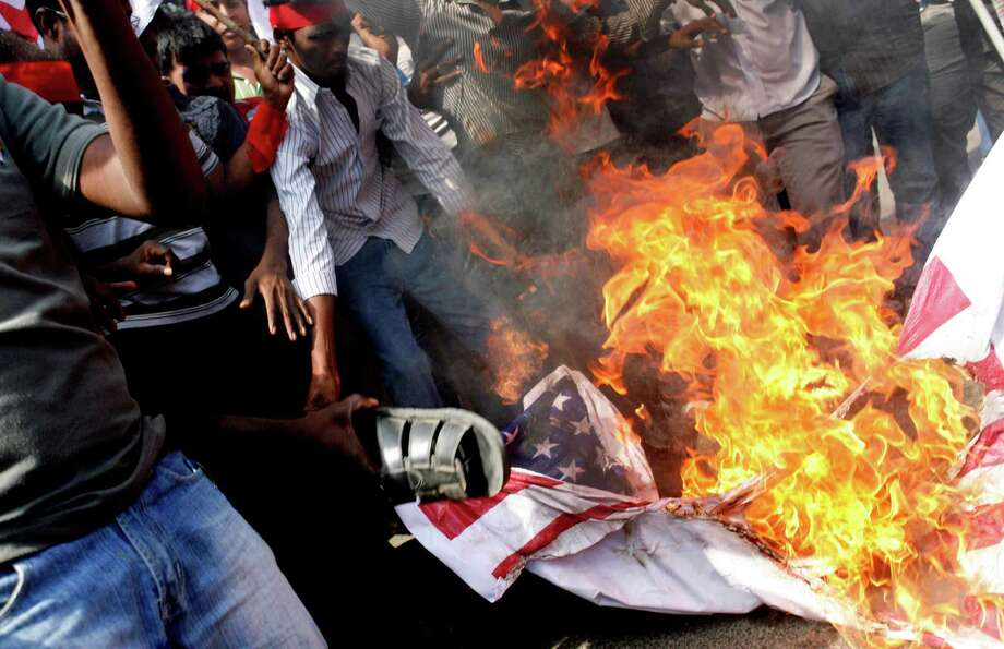 "Members of the Democratic Youth Federation of India (DYFI), burn a flag during a protest outside the U.S. consulate in Chennai, India, Saturday, Dec. 21, 2013. India's Information Minister Manish Tewari lashed out at the United States on Friday and demanded an apology for the treatment and arrest of Devyani Khobragade, India's deputy consul general in New York, saying America cannot behave ""atrociously"" and get away with it. Photo: Arun Sankar K, AP / AP2013"