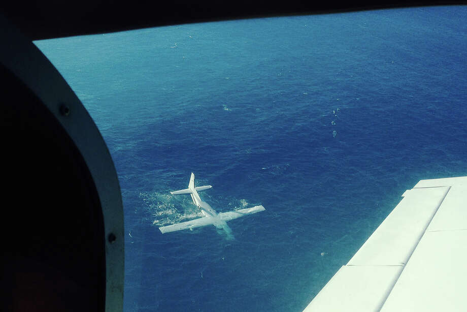 In this Dec. 11, 2013 photo provided by pilot Josh Lang, a single-engine plane is shown in waters off the island of Molokai following a crash shortly after takeoff toward Honolulu, Hawaii. One passenger died, eight other survived, including the pilot. The pilot of the plane that crashed off Molokai said Wednesday Dec. 18, 2013, he broadcast a mayday call once he realized he wouldn't be able to sustain a glide long enough to reach land after his engine lost power. Photo: Josh Lang, AP / Josh Lang