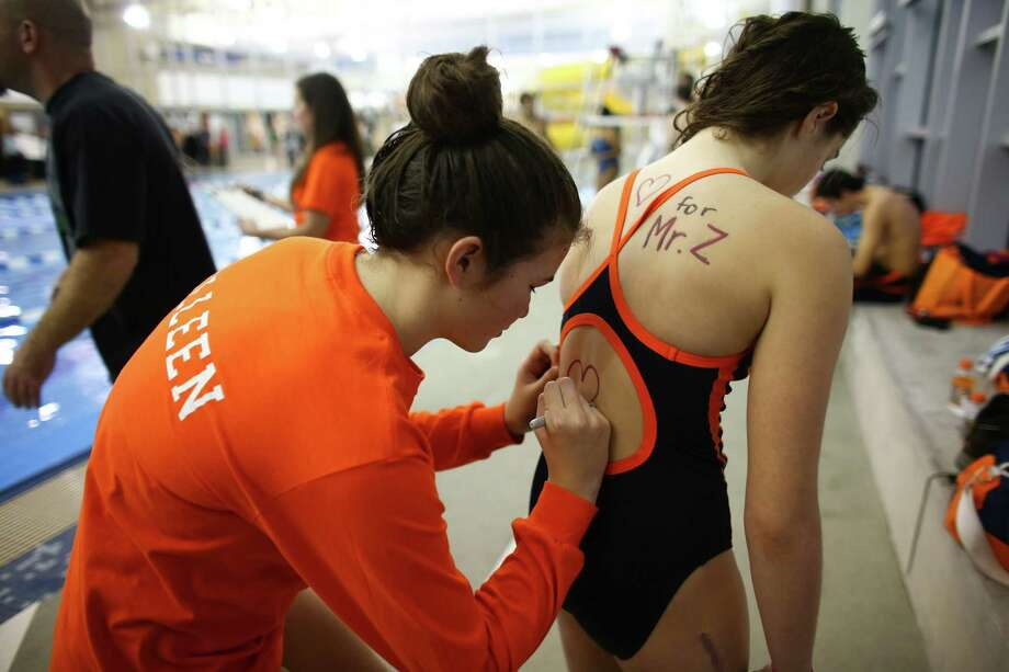 Swim team members write messages of support for their coach on each other's backs during a swim meet at the Rainier Beach Community Center, Friday, Dec. 20, 2013, in Seattle. Eastside Catholic's Vice Principal Mike Zmuda, who coached the team, resigned from the school after officials with the Seattle archdiocese discovered that he was in a same-sex marriage. He was told the marriage violated his contract. Photo: Joshua Trujillo, AP / seattlepi.com