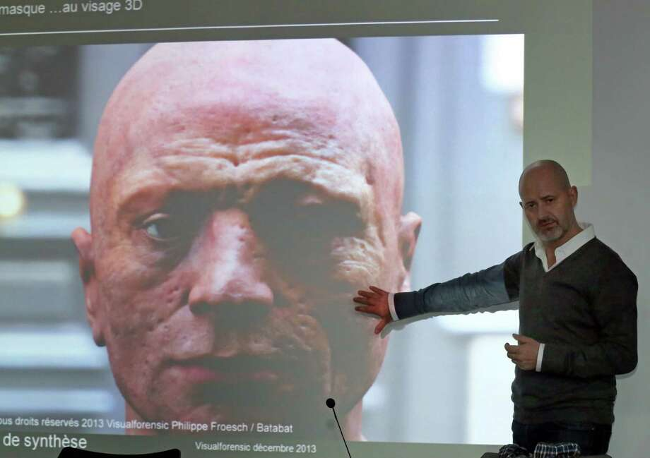 French researcher Philippe Froesch comments on a photo of the reconstructed Robespierre' face as he addresses reporters, during a press conference in Montigny, west of Paris, Friday Dec. 20, 2013. Using a death mask that some historians believe was taken by Madame Tussaud herself just after Maximilian de Robespierre was guillotined, the researchers constructed a pockmarked, malevolent face that bears little resemblance to portraits of the revolutionary leader.(AP Photo/Remy de la Mauviniere)  shows wrinkles on the death mask of French revolution figure Robespierre, during a press conference in Montigny, west of Paris, Friday Dec. 20, 2013. Using a death mask that some historians believe was taken by Madame Tussaud herself just after Maximilian de Robespierre was guillotined, the researchers constructed a pockmarked, malevolent face that bears little resemblance to portraits of the revolutionary leader. Photo: Remy De La Mauviniere, AP / AP