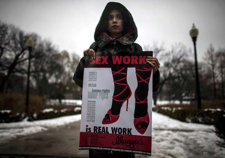A woman, who requested to withhold her name, holds a sign during a rally at Allan Gardens park to support Toronto sex workers and their rights in Toronto, Friday Dec. 20, 2013. Canada's highest court struck down the country's anti-prostitution laws Friday, a victory for sex workers who had argued that a ban on brothels and other measures made their profession more dangerous. Photo: Mark Blinch, AP / The Canadian Press