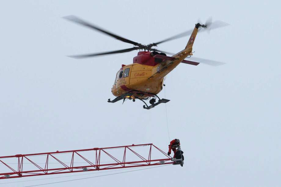A rescue worker is lowered from a Canadian military helicopter as they retrieve a crane operator who was stranded atop a crane when fire broke out in an apartment building under construction in downtown Kingston, Ontario, Tuesday, Dec. 17, 2013. The crane operator was taken to a waiting ambulance, and police say he was believed to have only minor injuries. Photo: Lars Hagberg, AP / CP