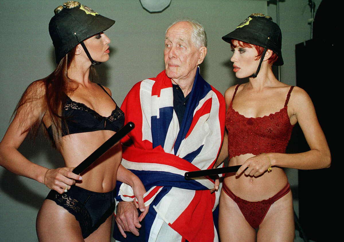 This Jan. 25, 2001 file photo shows Ronnie Biggs, one of Britain's most notorious criminals, wrapped in a Union Jack flag, posing for photos with lingerie models Milene Zardo, left, and Francine Mello equipped with English police helmets and batons in Rio de Janeiro, Brazil. Biggs, known for his role in the 1963 Great Train Robbery, died Wednesday, Dec. 18, 2013, his daughter-in-law said. He was 84.
