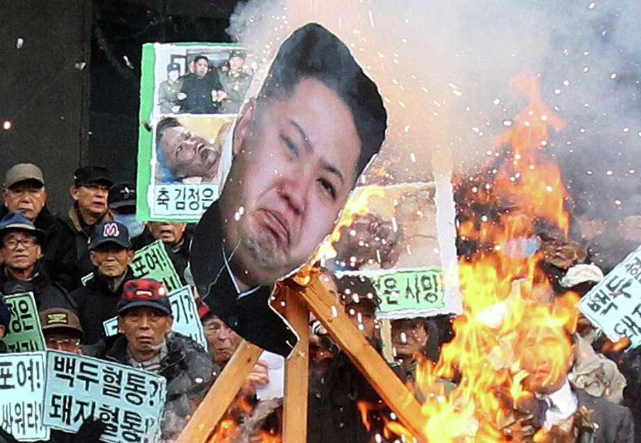 A portrait of North Korean leader Kim Jong Un is burned by protesters during an anti-North Korea rally marking the second anniversary of former North Korean leader Kim Jong Il's death in Seoul, South Korea, Tuesday, Dec. 17, 2013. Photo: Ahn Young-joon, AP / AP2013