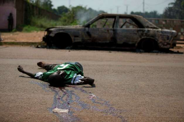 A man lies dead at a checkpoint beside a burnt out car, following a shootout with Congolese peacekeepers, in Bangui, Central African Republic, Friday, Dec. 20, 2013. Three bodies lay baking in the sun at the checkpoint Friday after being shot by Congolese peacekeepers, who said the men had attacked them. After a period of relative calm, violence has flared anew in the Central African